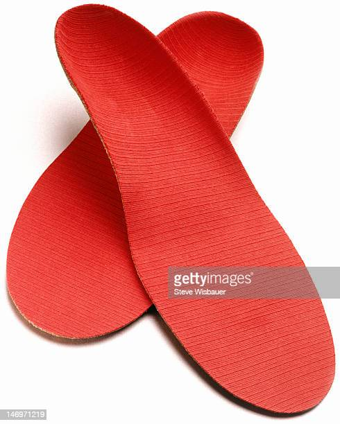 A pair of red orthopedic shoe insoles