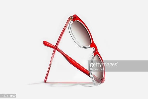 A pair of red sunglasses on a white background