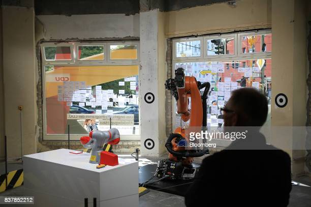 A pair of robotic arms manufactured by Kuka AG stand at interactive display inside the Christian Democratic Union walkin manifesto located inside a...