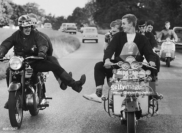Pair of Rockers British youths into leather motorcycles zip past a rival group of Mods British youths into fashionable clothes and fancy scooters