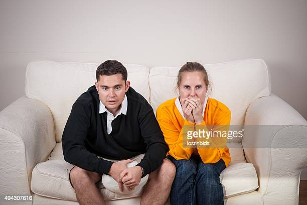 Pair Of Rugby Fans On Rival Team Watching Tense Match