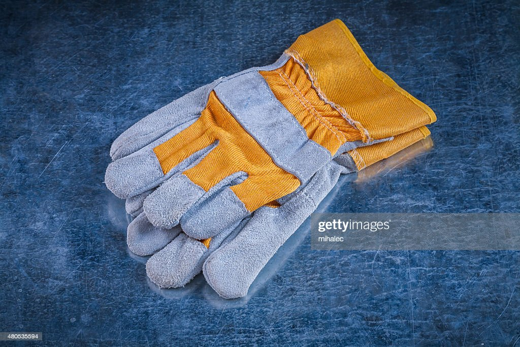 Pair of safety working gloves on scratched vintage metallic back : Stock Photo