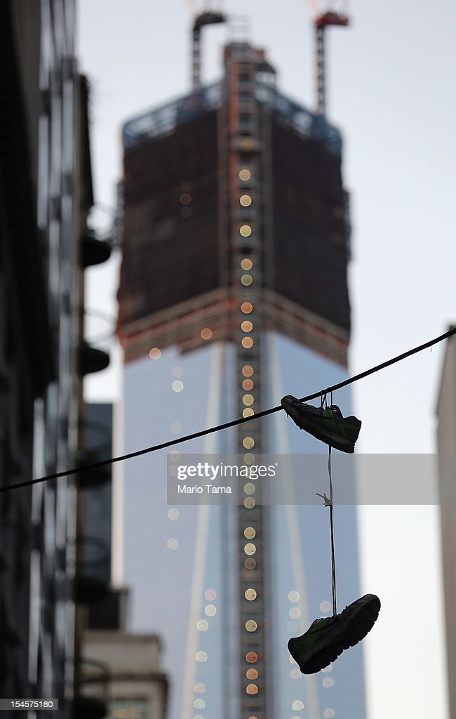 A pair of shoes dangle from a wire in Lower Manhattan as One World Trade Center rises under construction in the background on October 22, 2012 in New York City. The Census Bureau reported last month that between 2000 and 2010 the downtown population grew by nearly 40,000 people, in spite of the September 11 terrorist attacks at the World Trade Center. One World Trade Center is scheduled to open in 2014 at the symbolic height of 1,776 feet and will be the tallest building in the Western Hemisphere.