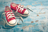 Pair of red sneakers on wooden background with empty space