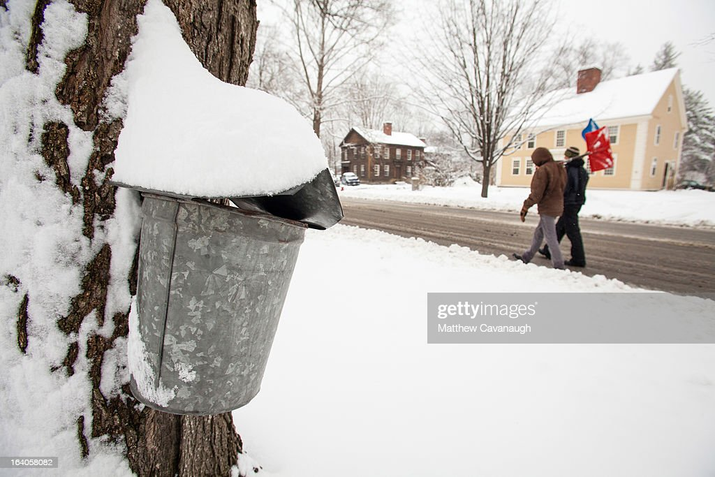 A pair of snow shovelers walk past a maple sap collection bucket along Main Street in the historic village of Old Deerfield on March 19, 2013 in Deerfield, Massachusetts. Another winter storm blew through the Northeast yesterday, with snow and sleet closing schools in some areas and making for a messy morning commute.