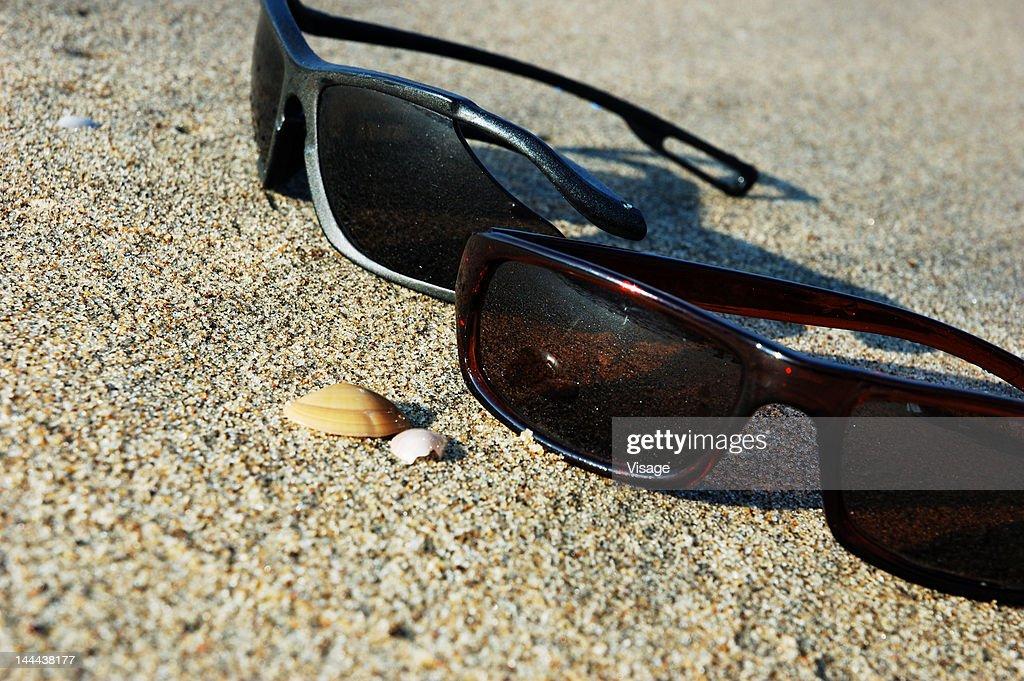 Pair of sunglasses lying on the beach : Stock Photo