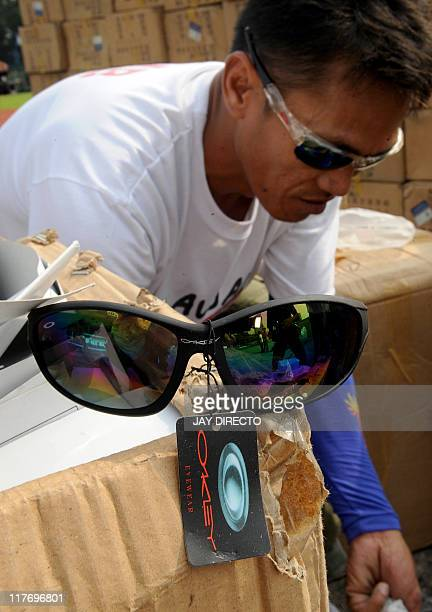 A pair of sunglasses sits on to of a box as a government official helps to destroy 8 million USD worth of counterfeit shoes bags medicine books...