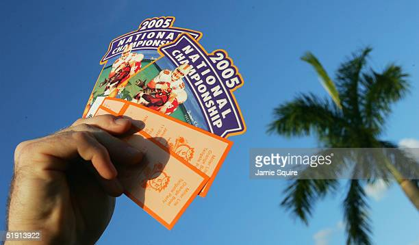 A pair of tickets are heldup by a fan outside in the parking lot before the start of the FedEx Orange Bowl 2005 National Championship between the USC...