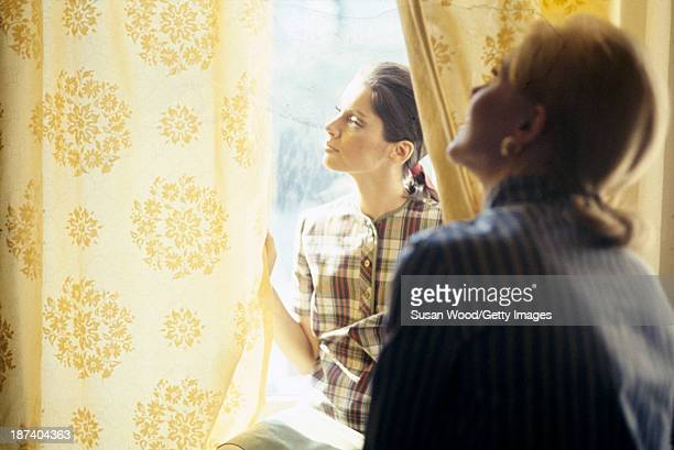 A pair of unidentified models one in a yellow red and black plaid top look at yellow print curtains in a window August 1965