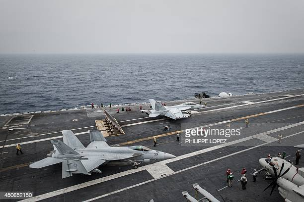 A pair of US Navy Boeing F/A18 Super Hornet aircraft prepare for a catapult launch from the flight deck of the US nuclearpowered aircraft carrier USS...