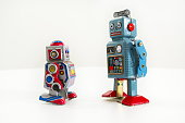 Two vintage tin toy robots isolated on white background