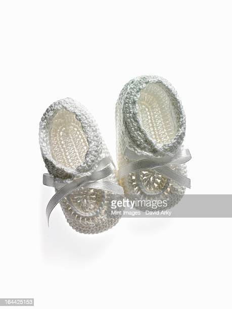 A pair of white baby booties, shoes for infants.