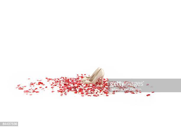 pair of white high heels on patch of rose petals