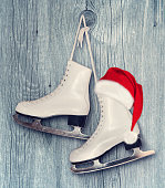 Pair of White Ice Skates and Santa Claus hat - backround on vintage, retro style.