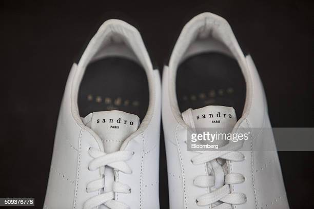 A pair of white sneakers sit on display inside a Sandro luxury clothing store operated by SMCP Group in Toulouse France on Wednesday Feb 10 2016...