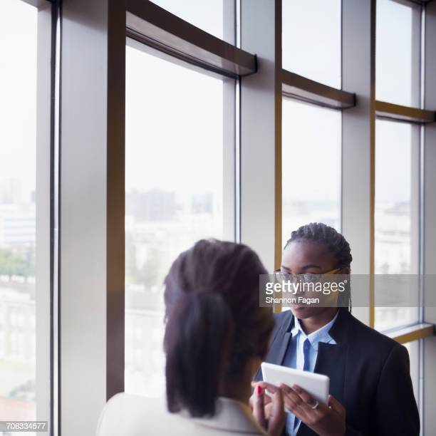 Pair of women talking in office next to window