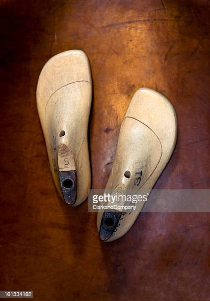 Pair of Wooden Shoe Last on Leather Background.