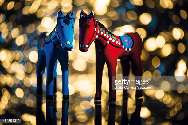 A pair of wooden toy horses photographed against a glittering bokeh background taken on October 16 2014