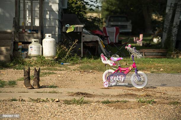 A pair of work boots sits out to dry next to a little girls training bike in a front yard in Bainville MT Sept 14 2013 Back in 2008 the North Dakota...