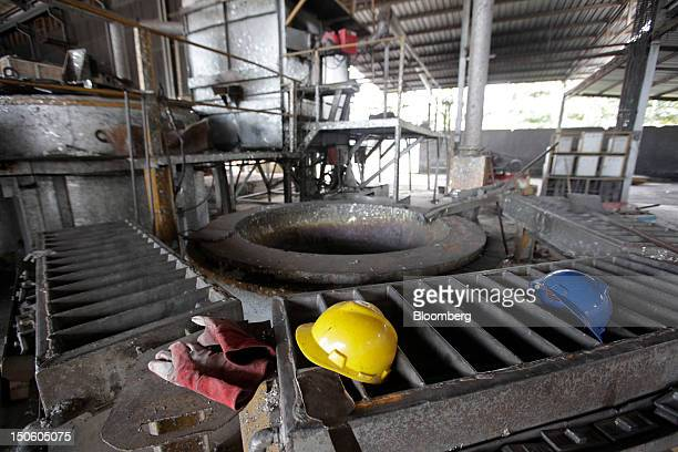 A pair of workers' gloves and safety hats lay on top of machinery in a tin smelter owned by Johan Murod a private tin refiner in Pangkal Pinang...