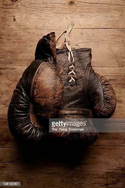 A pair of worn old boxing gloves on wooden table