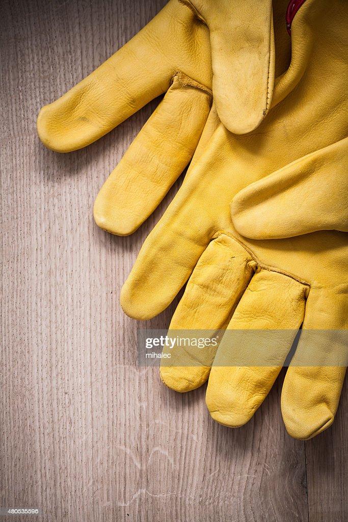 Paar gelbem Leder Schutzhandschuhe auf hölzernen Hintergrund ag : Stock-Foto