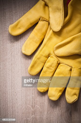 Pair of yellow leather protective gloves on wooden background ag : Stock Photo