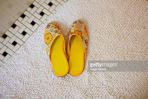 Pair of yellow slippers on rug
