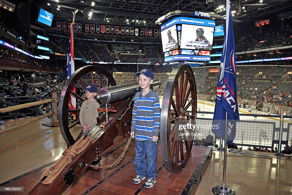 A pair of young Columbus Blue Jackets fans pose next to the cannon for a photo before the game between the Columbus Blue Jackets and the Chicago...