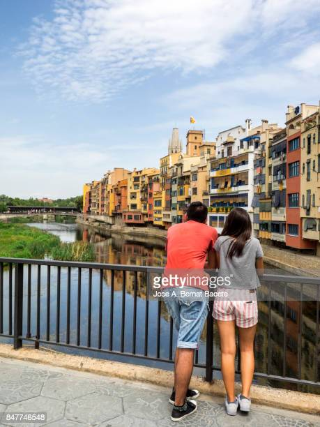A pair of young women looking from on a bridge, cathedral and houses on Onyar riverbank, Spain, Catalonia, Girona.