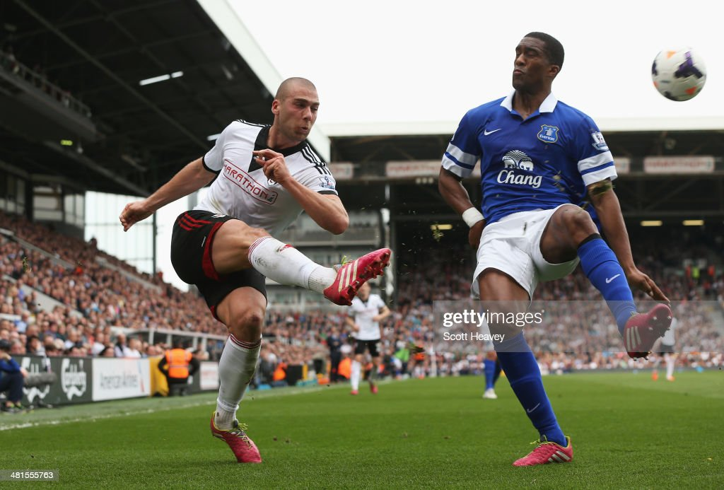 Pajtim Kasami of Fulham crosses as he is closed down by Sylvain Distin of Everton during the Barclays Premier League match between Fulham and Everton at Craven Cottage on March 30, 2014 in London, England.