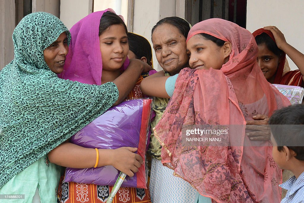 Pakistan and Myanmar women prisoners hug each other after receiving ladies suits gifted by members of Al-Habib Trust's during the month of Ramadan at the central jail on the outskirts of Amritsar on July 29, 2013. Tens of millions across the Muslim world fast from dawn to dusk and strive to be more pious and charitable during the month, which ends with the Eid holiday.