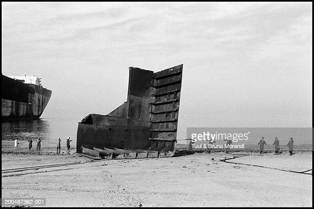 Pakistan, Balouchistan, Gadani Beach, men dismantling cargo ship (B&W)
