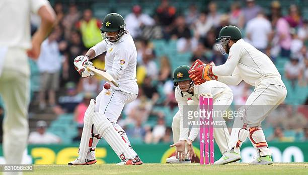 Pakistan batsman Sharjeel Khan cuts a ball away as Australia's Matthew Wade and Peter Handscomb look on on the fourth day of the third cricket Test...