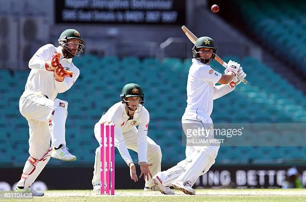 Pakistan batsman Yasir Shah cuts the ball away as Australia's wicketkeeper Matthew Wade and fieldsman Peter Handscomb look on during the final day of...