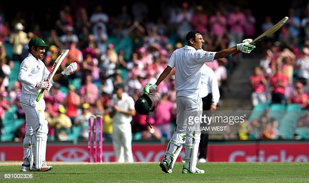 Pakistan batsman Younis Khan celebrates scoring his century against Australia as teammate Sarfraz Ahmed applauds during the third day of the third...