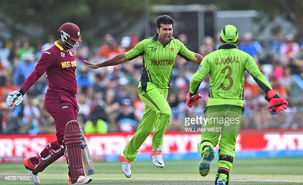 Pakistan bowler Sohail Khan celebrates with teammate Umar Akmal after dismissing West Indies batsman Dwayne Smith during their 2015 Cricket World Cup...