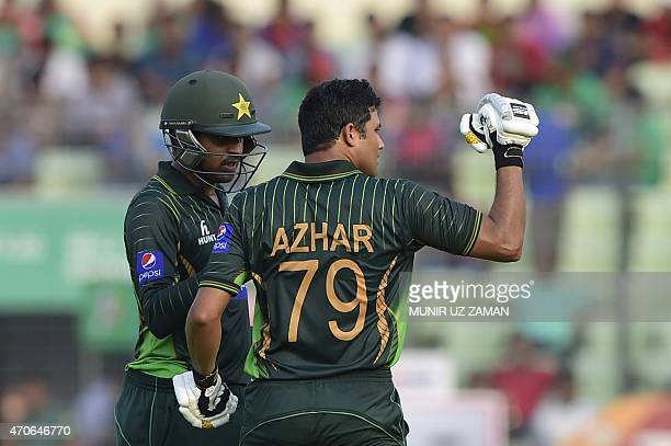 Pakistan captain Azhar Ali reacts after scoring a century as his teammate Haris Sohail congratulates him during the third One Day International...