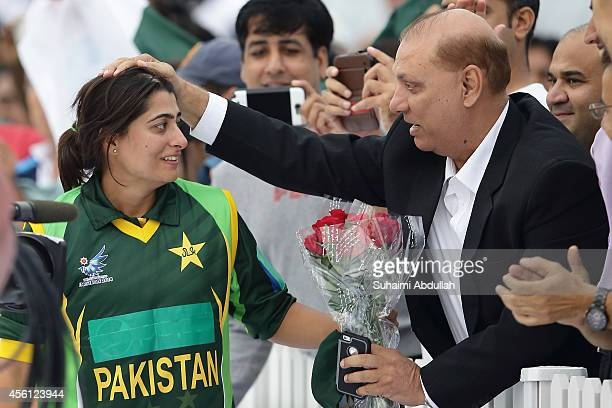 Pakistan captain Sana Mir receives a bouquet of flowers ater helping Pakistan to beat Bangladesh to win the gold in the cricket women's final on day...