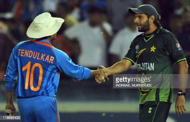 Pakistan captain Shahid Afridi greets Indian cricketer Sachin Tendulkar after the second semifinal match of The ICC Cricket World Cup 2011between...