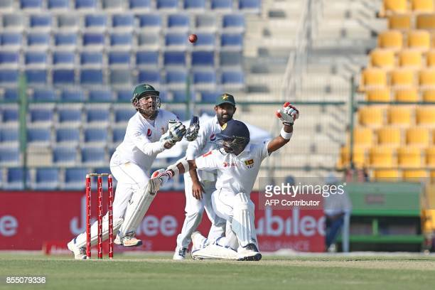 Pakistan cricket captain and wicketkeeper Sarfraz Ahmed tries to catch a ball on the first day of the first Test cricket match between Pakistan and...