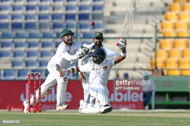 Pakistan cricket captain and wicketkeeper Sarfraz Ahmed trying to catch a ball on the first day of the first Test cricket match between Pakistan and...