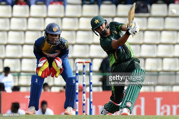 Pakistan cricket captain Azhar Ali plays a shot as Sri Lankan wicketkeeper Dinesh Chandimal looks on during the second One Day International match...