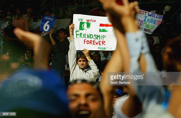 Pakistan cricket fan holds a sign which says 'We Wish Pakistan and India Friendship Forever' while watching the game from the stand during the first...