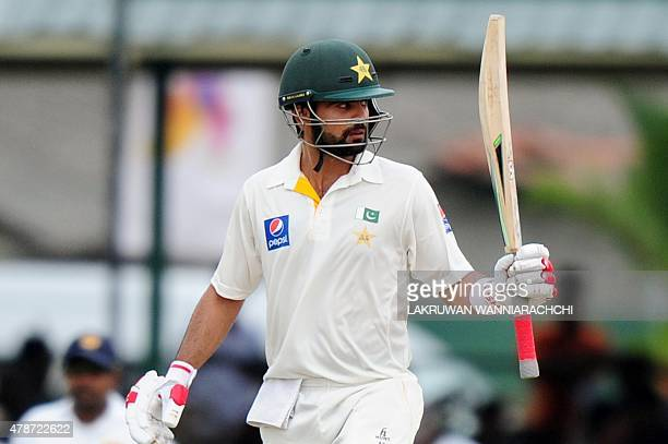 Pakistan cricketer Ahmed Shehzad raises his bat to the crowd after scoring a halfcentury during the third day of the second Test match between Sri...