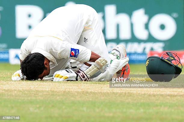 Pakistan cricketer Azhar Ali raises touches the ground after scoring a century during the fourth day of the second Test match between Sri Lanka and...