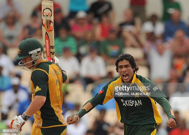 Pakistan cricketer Mohammad Aamer celebrates the wicket of Australian cricketer David Warner during the ICC World Twenty20 second semifinal match...