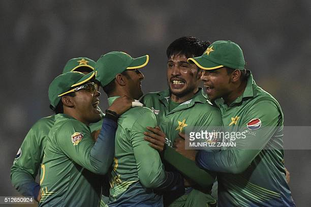 Pakistan cricketer Mohammad Amir celebrates with teammates after the dismissal of Indian cricketer Suresh Raina during the match between India and...