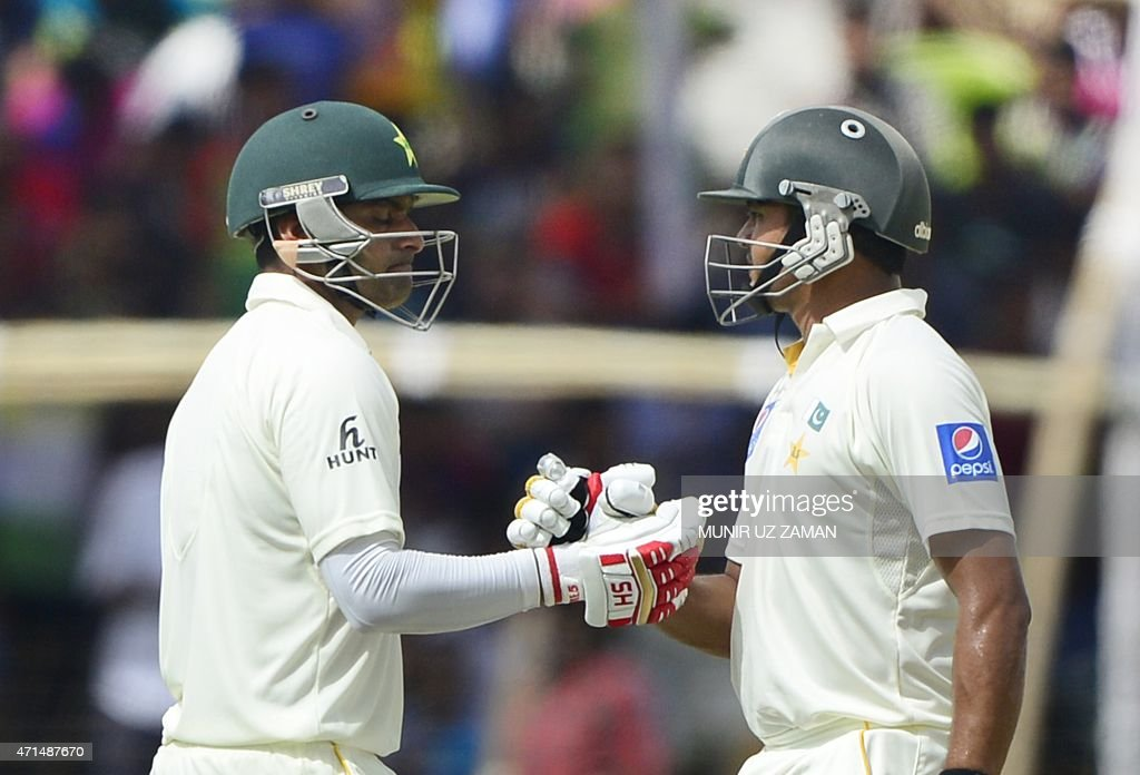 Pakistan cricketer Mohammad Hafeez celebrates his half century with teammate Azhar Ali during the second day of the first cricket Test match between...
