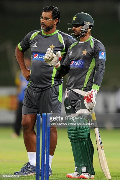 Pakistan cricketer Mohammad Hafeez speaks with coach Waquar Younis during a practice session at the Pallekele International Cricket Stadium in...